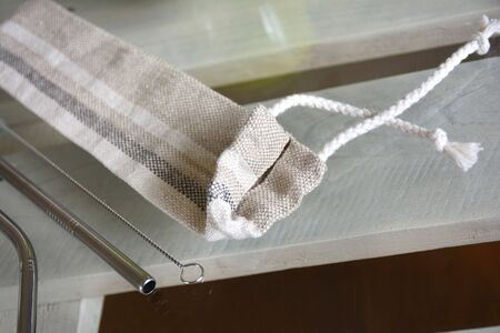 Reusable zero waste stainless steel straw set and linen pouch, close-up view