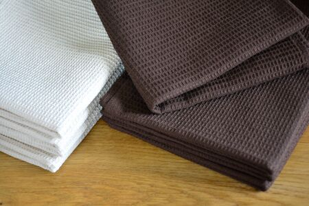 Waffle weave kitchen or hand towels on wooden table. Home textile