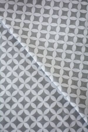 White and grey overlapped circles pattern fabric sample. Folded fabric background 스톡 콘텐츠