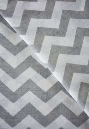 White and grey chevron pattern fabric sample. Folded fabric background 스톡 콘텐츠