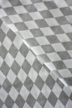 White and grey rhombus harlequin pattern fabric sample. Folded fabric background