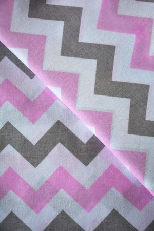 Pink, white and grey chevron pattern fabric sample. Folded fabric background