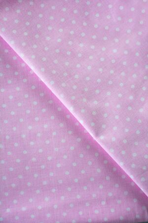 Pink polka dot fabric sample. Folded fabric background
