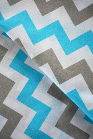 Sky blue, white and grey chevron pattern fabric sample. Folded fabric background