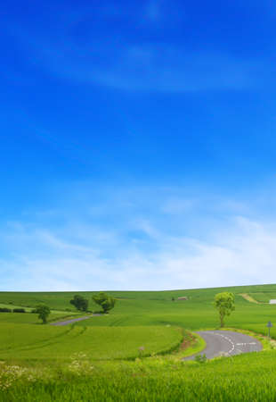 A winding road road in the field and blue sky