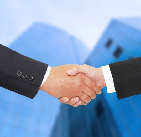 success deal shake hand in front of a building photo