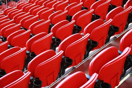 rows of red seat at a stadium photo