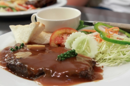 a plate of beef steak with pepper gravy photo