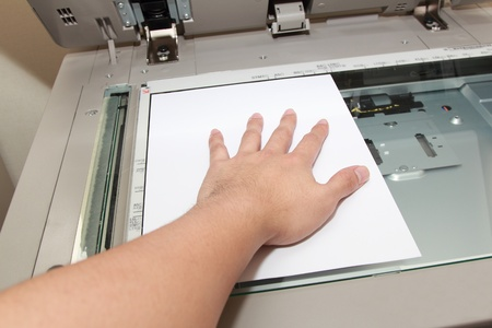 hand pressing paper on a copy machine photo