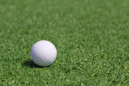 golf ball on a green in a sunny day photo