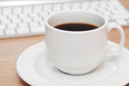 cup of espresso in front of keyboard