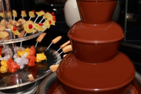 chocolate fountain with fruit and marshmallow background