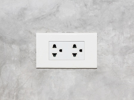 wall socket: electric socket on a concrete wall Stock Photo