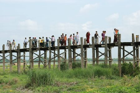 MANDALAY - May 24 : The villagers walking on U-Bein bridge, May 24, 2010, Mandalay, Myanmar. The U-Bein bridge is the longest teak bridge in the  world