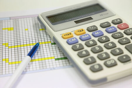 pen and calculator for financial calculating on the office table photo