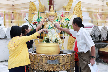 YANGON, MYANMAR -MAY 27: people pouring water over the head of Buddha at Shwedagon Pagoda, in Yangon on 27 May 2013.