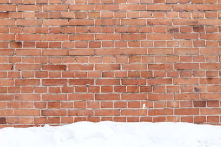 background of brick wall with the snow on the ground photo