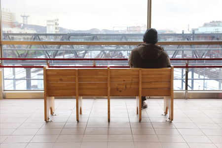 mature man sitting alone on bench in the train station in winter photo