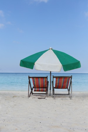beach chairs with umbrella om the sand in nangyuan island thailand photo