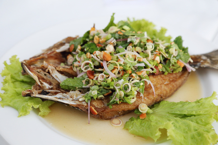 fried fish with fresh herbs and sweet spicy sauce photo
