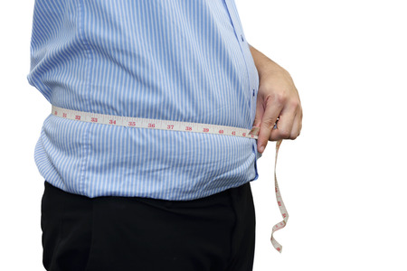 isolated fat man measuring his belly with the tape on white background