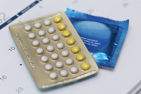 birth control pills and condom on a calendar 스톡 콘텐츠