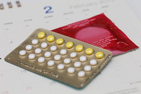 birth control: las p�ldoras anticonceptivas y preservativos en un calendario