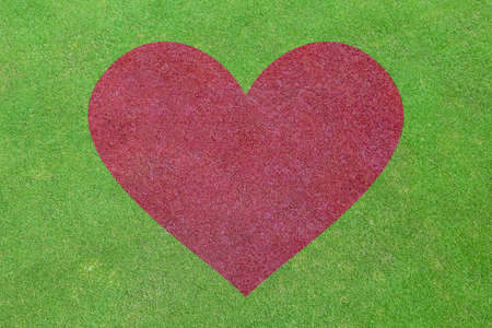 love symbol: background of green grass field with red heart shape Stock Photo