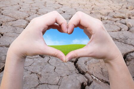 hope: background of hand in heart shape with green field inside on the crack earth Stock Photo