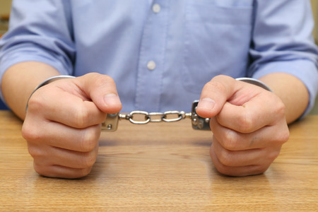 business hand arrested with handcuffs on the wooden table photo