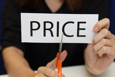 price cutting: Closeup on woman cutting paper of price word Stock Photo