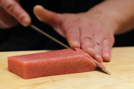 chefs: hand of japanses sushi chef slice a fresh raw sashimi Stock Photo