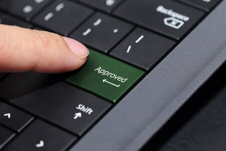 approved button: background of finger pushing on  the approved button on laptop  keyboard