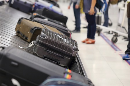 conveyor belts: image of people picking up suitcase on luggage conveyor belt in the  airport