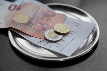 taxable income: euro bank note payment for bill on on restaurant table
