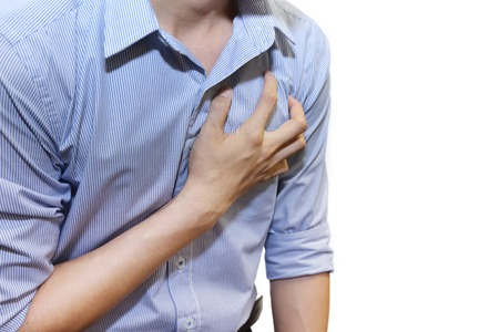 palpitation: isolated man having a heart attack grab his chest with pain