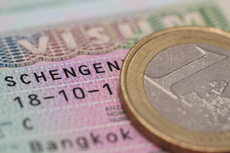 schengen: close up schengen visa in the passport with euro coin