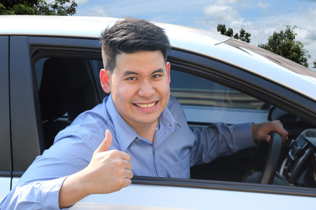 automobile insurance: asian business man with thumb up gesture in a car