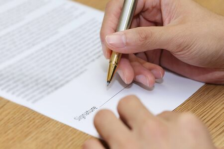 assent: close-up on a businessman hand signing a contract paper Stock Photo
