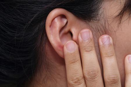 dolor de oido: en primer plano en mano de la mujer tocar su oído con el dolor