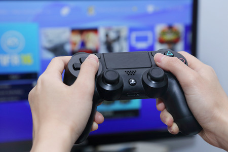THAILAND -OCTOBER 2: Hand Playing Sony Dualshock 4 Controller for PlayStation 4 with the Screen on the background  taken in BANGKOK THAILAND on October 2, 2015. Editorial