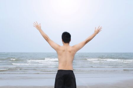 spreading arms: rear view of asian man spreading arms and watching the ocean Stock Photo