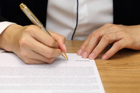 indenture: close-up on a businessman hand signing a contract paper Stock Photo
