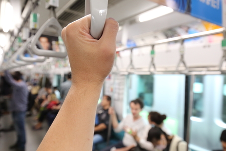 transportaion: man hand holding onto a handle of a train