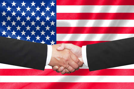 syndicate: two businessmen shakehand over american national flag