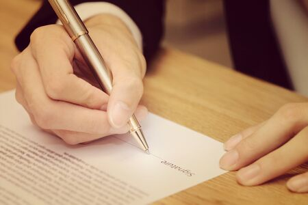 indenture: close-up on a businessman hand signing a contract paper in vintage style