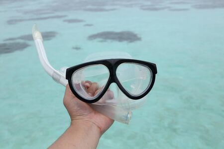 snorkelers: background of hand holding a diving mask and a snorkel Stock Photo