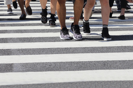 crossing legs: close-up on unidentified people legs crossing street