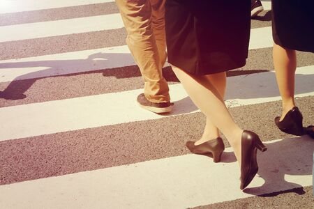 crossing street: close-up on unidentified people legs crossing street in vintage style Stock Photo