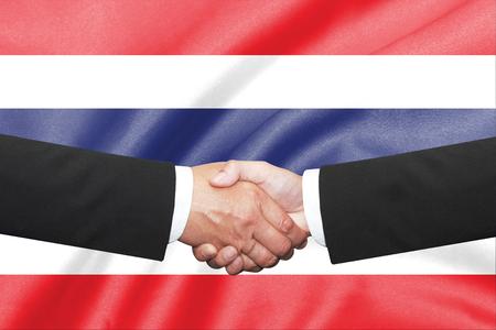 thai flag: two businessman shakehand over thai flag background
